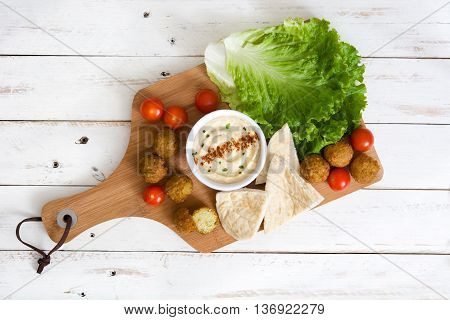 Vegetarian falafel ball with hummus on white wooden table