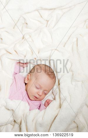 Little cute newborn baby sleeping on its back on a soft blanket. Healthy infant sleep.