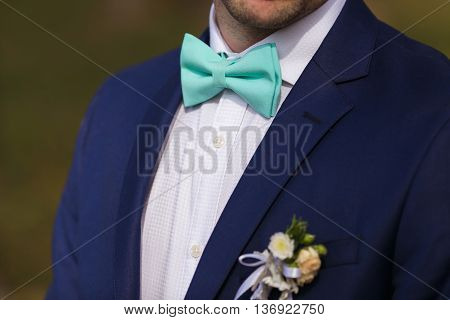 Groom set the bowtie straight close up