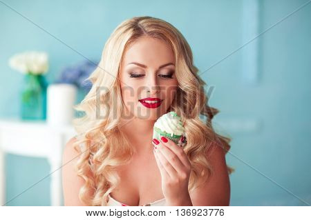 Smiling beautiful blonde woman 25-27 year old eating cupcake in room over blue. Unhealthy lifestyle.