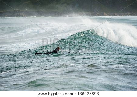 CULLEN SCOTLAND - OCTOBER 21 2013: A surfer heading to beach while surfing near Cullen in Scotland during winter.