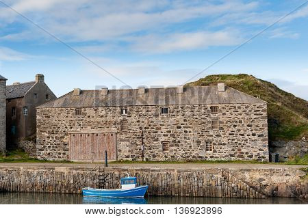 Portsoy harbour with small blue boat and old stone store building.