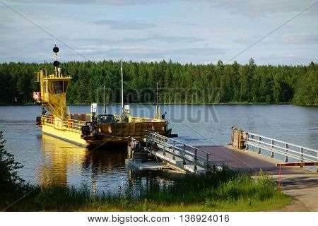 TAIPALSAARI, FINLAND - JULY 2: Yellow cable ferry carrying passengers and cars across Kutvele canal on lake Saimaa in Eastern Finland arriving to the landing dock in Kyläniemi on calm summer evening July 2, 2015 in Taipalsaari, Finland.