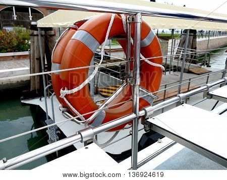 Orange life buoy on ship for emergency with ropes