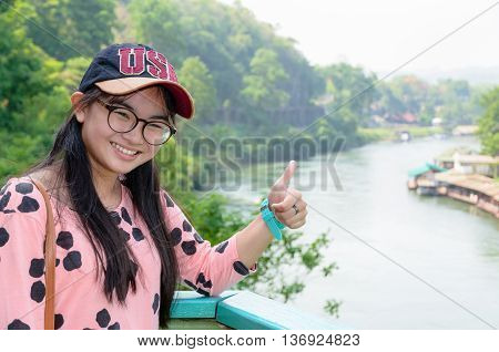 Tourist girl show thumb appreciate the beautiful landscape of Death Railway bridge over the Kwai Noi River at Krasae cave viewpoint in Kanchanaburi province Thailand