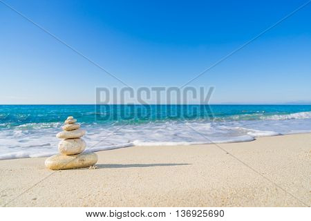 Stones pyramid on sand symbolizing zen, harmony, balance. Ocean in the background