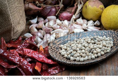 Spices many with Pepper in ladle on dark wooden table