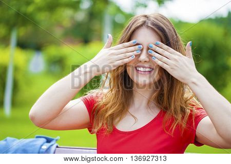 Happy Young girl closes eyes with her hands
