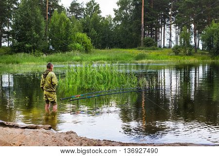 The river Ob Novosibirsk oblast Siberia Russia - July 4 2016: a fisherman with float rod fishing summer on the river standing in water