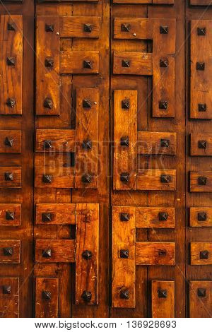 Door of orange old barn boards with metal iron decorative rivets on timber background