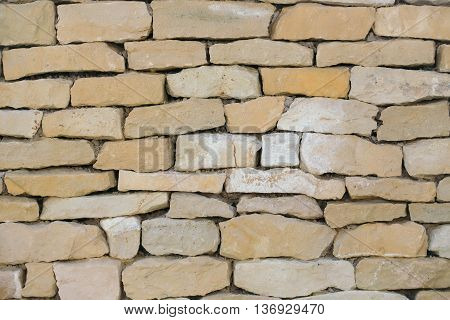 Old brick wall of beige uneven cracked stone surface on mason background