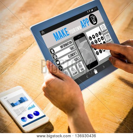 Make your own app smartphone against over shoulder view of casual man using tablet