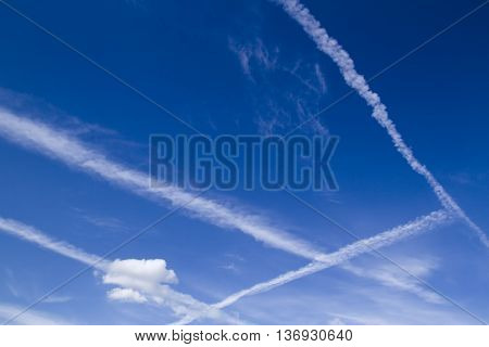 Blue sky with many white clouds lines made of aircraft background