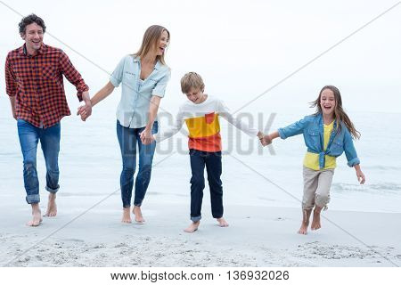 Full length of cheerful family holding hands while walking at sea shore
