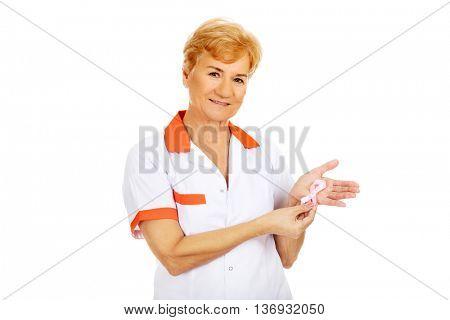 Elderly female doctor or nurse holds pink breast cancer awareness ribbon