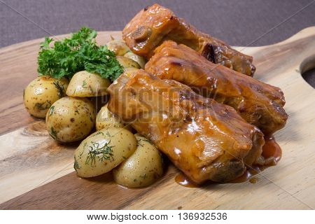 Fried pork ribs with potatoes on a wooden board