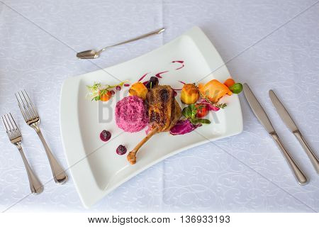Confit duck or goose leg crisp delicious served with garnish red tomatoes vegetables and blackberry sauce on white background