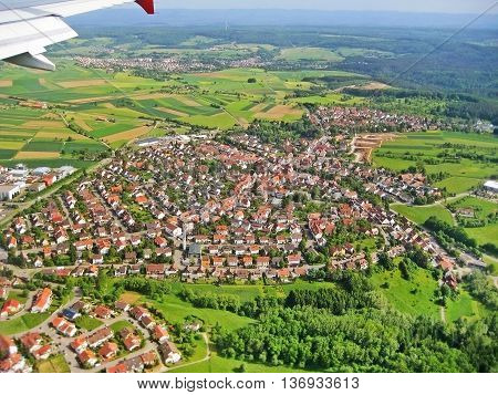 Typical german village during landing approach surrounded by fields and forest aerial view