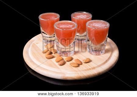 Liquor shots with almonds on wooden board