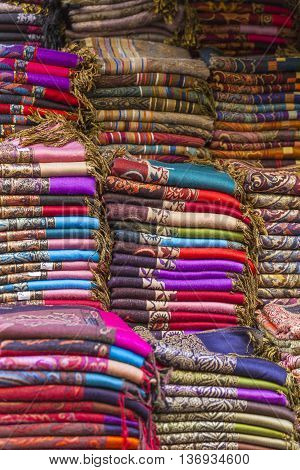 Colorful fabrics and carpets for sale on a street in Medina of Essaouira Morocco