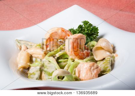 Green noodles with prawns and scallop served on a white plate