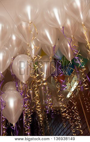 Flying white balloons with ribbons filled with helium