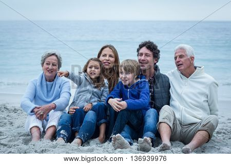 Smiling family looking away while sitting at beach