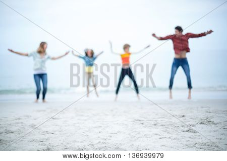 Defocused image of family jumping with arms outstretched at sea shore