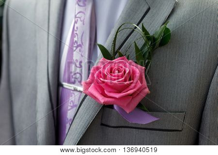 Grey jacket and beautiful groom's boutonniere. Red Rose