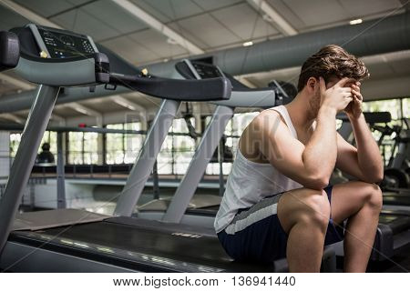 Tired man sitting on treadmill at gym