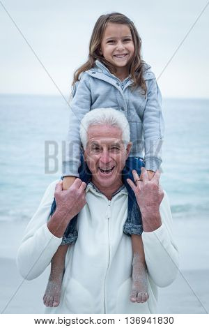 Portrait of smiling grandfather carrying granddaughter on shoulders at beach