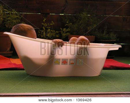 Child Playing In A Small Plastic Washtub