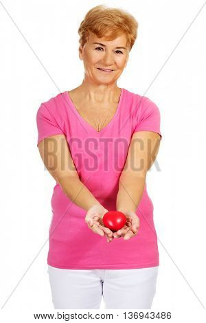 Old smiling woman holding red toy heart