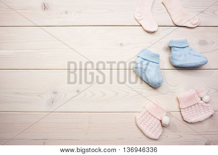 Cute baby girl and baby boy socks on blank wooden surface. Mock up