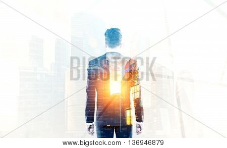 Back view of businessman on city background with sunlight. Double exposure