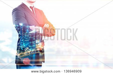 Businessman with crossed arms and illuminated night city on light background with copy space