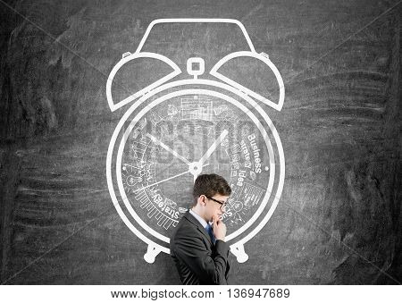 Time management concept with thoughtful businessman against chalkboard wall with alarm clock sketch