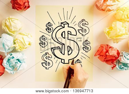 Financial growth concept with hand drawing dollar signs on paper sheet surrounded with colorful crumpled paper balls