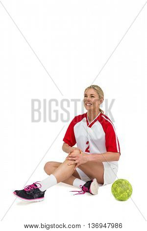 Sportswoman touching her knee on white background