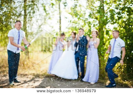 Blur focus photo of wedding couple with groomsman and bridesmaid with champagne explosion