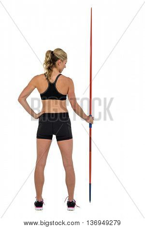 Rear view of athlete standing with javelin on white background