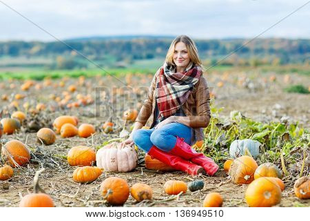 Beautiful young woman in red rain boots working on pumpkin farm or patch. Girl having fun with farming. Thanksgiving, harvest or halloween concept