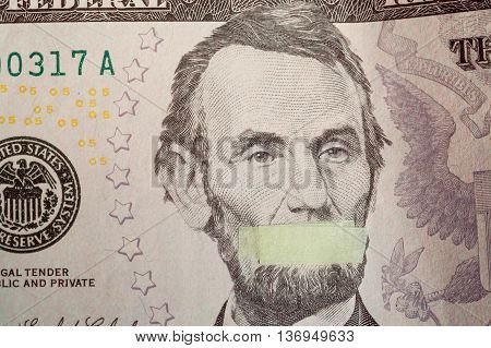 Silente president portrait of the American leader Abraham Lincoln with mouth closed on the banknote of five dollars USA as a symbol of the instability of the modern economy