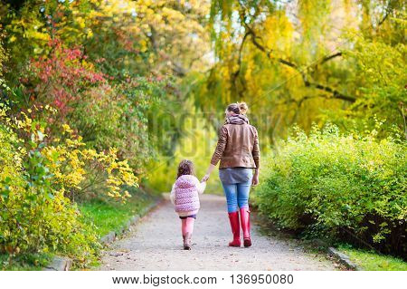 Young mother and her little daughter at beautiful autumn park. Kid girl and beatiful woman in gumboots walking and having fun. Family portrait outdoors.