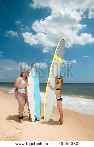 Beautiful young fat and skinny women at the summer sea with the surfboards