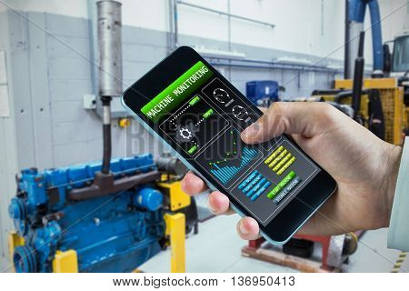 hand holding smartphone against image of machinery