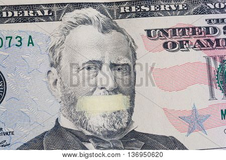 Silente president portrait of the American leader Ulysses Grant with mouth glued on the banknote of fifty dollars USA as a symbol of the instability of the economy system