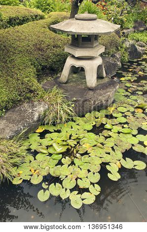 ancient stone lantern structure on pond shore in Japanese zen garden by summer