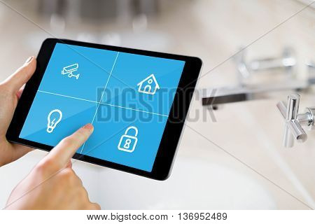 Man using tablet pc against close up of bathroom sink
