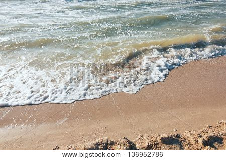 Turquoise sea wave foam on beach. Beautiful water nature. Perfect summer resort for relax. Sea waves near beach. Beautiful sea beach. Summertime, blue sea and waves, yellow sun and sand.